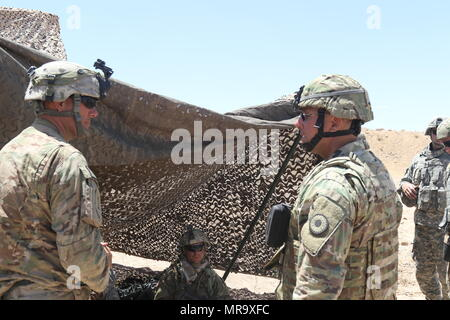 Maj. General Lee Tafanelli, the adjutant general of Kansas, speaks with Sgt. David Ibarra of the 2d Battalion, 137th Infantry Regiment of the Kansas Army National Guard, on how Soldiers develop experience from being in a simulated combat environment, May 28, 2017 at the National Training Center, at Fort Irwin, California. (Mississippi National Guard photo by Sgt. DeUndra Brown, 102d Public Affairs Detachment) - Stock Photo