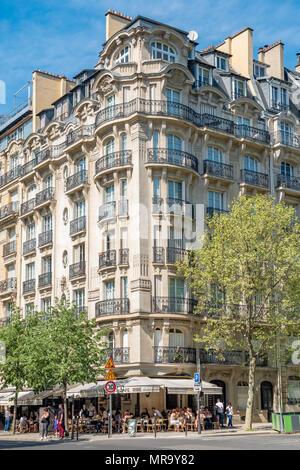 A typical Paris apartment building with intricate details and wrought iron with a small cafe occupying the ground level. - Stock Photo