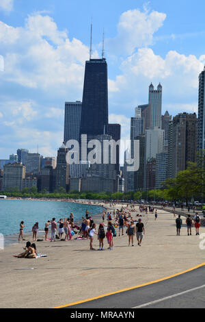 Chicago Illinois, USA - May 25 2018: People head to the Concrete Beach on Chicago's north side as air temperatures approach 90 deg. (F), 32 deg. (C) for the start of the long Memorial Day weekend. But most are staying out of the water as Lake Michigan is a cold 50 deg. (F), 10 deg. (C.) Credit: D Guest Smith/Alamy Live News - Stock Photo