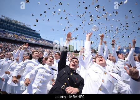 U.S. Naval Academy graduates toss their hats into the air during the annual tradition marking their commissioning and graduation May 25, 2018 in Annapolis, Maryland. The Class of 2018 graduated 1,042 midshipmen and was addressed by President Donald Trump during the ceremony. - Stock Photo