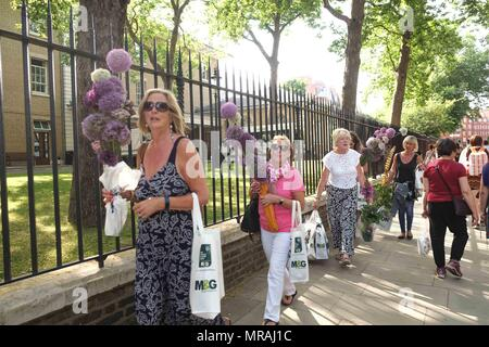 London,UK 26th May 2018: Visitors to the Chelsea Flower Show 2018 leave on the final day with heavily discounted flowers and plants.Credit: Claire Doherty/Alamy Live News - Stock Photo