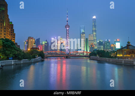 Famous skyline of Pudong in Shanghai, China with many landmark buildings along the Huangpo River including the Pearl Tower - Stock Photo