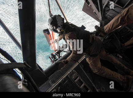 ARABIAN GULF (May 27, 2017) Naval Air Crewman (Helicopter) 2nd Class Anaeto Chinemere, assigned to the Blackhawks of Helicopter Mine Countermeasures Squadron (HM)15, prepares a Q-24 sonar side-looking vehicle to be lowered into the Arabian Gulf from an MH-53E Sea Dragon helicopter during mine countermeasure exercise Artemis Trident 2017, May 27.  Artemis Trident is an international exercise, which focuses on the protection of sea-lanes and the free travel of international commerce. (U.S. Navy Combat Camera photo by Mass Communication Specialist 1st Class Joshua Bryce Bruns) - Stock Photo