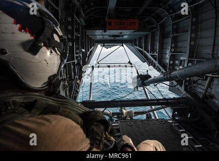 ARABIAN GULF (May 27, 2017) Naval Air Crewman (Helicopter) 2nd Class Anaeto Chinemere, assigned to the Blackhawks of Helicopter Mine Countermeasures Squadron (HM) 15, monitors a Q-24 sonar side-looking vehicle being towed through the Arabian Gulf from an MH-53E Sea Dragon helicopter during mine countermeasure exercise Artemis Trident 2017, May 27.  Artemis Trident is an international exercise, which focuses on the protection of sea-lanes and the free travel of international commerce. (U.S. Navy Combat Camera photo by Mass Communication Specialist 1st Class Joshua Bryce Bruns) - Stock Photo