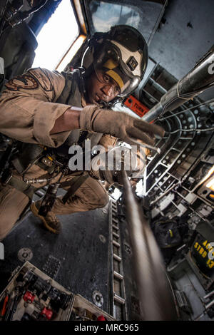 ARABIAN GULF (May 27, 2017) Naval Air Crewman (Helicopter) 2nd Class Anaeto Chinemere, assigned to the Blackhawks of Helicopter Mine Countermeasures Squadron (HM) 15, removes the tow ball from a tow line pulling a Q-24 sonar side-looking vehicle through the Arabian Gulf from an MH-53E Sea Dragon helicopter during mine countermeasure exercise Artemis Trident 2017, May 27.  Artemis Trident is an international exercise, which focuses on the protection of sea-lanes and the free travel of international commerce. (U.S. Navy Combat Camera photo by Mass Communication Specialist 1st Class Joshua Bryce  - Stock Photo