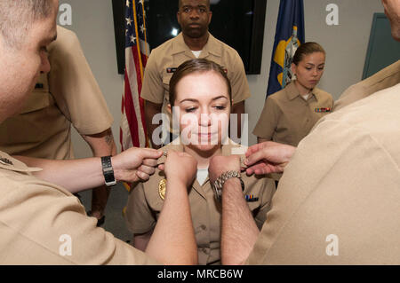 170602-N-EC644-015 MISAWA, Japan (June 2, 2017) Master-at Arms 3rd Class Koressa Huddleston, from Boise, Idaho, center, has her third class petty officer collar devices pinned on by fellow Sailors during a frocking ceremony at Naval Air Facility Misawa, Japan.  Huddleston is assigned to Naval Air Facility Misawa's Security Detachment and has been promoted one paygrade which comes with increased levels of leadership and responsibilities.  (U.S. Navy photo by Senior Chief Mass Communication Specialist Ryan C. Delcore) - Stock Photo