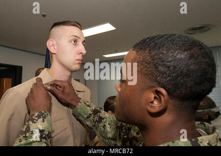 170602-N-EC644-020 MISAWA, Japan (June 2, 2017) Construction Electrician 3rd Class Blake Lyster, from Phoenix, left, has his third class petty officer collar devices pinned on by a fellow Sailor during a frocking ceremony at Naval Air Facility Misawa, Japan.  Lyster is assigned to Public Works Detachment Misawa and has been promoted one paygrade which comes with increased levels of leadership and responsibilities.  (U.S. Navy photo by Senior Chief Mass Communication Specialist Ryan C. Delcore) - Stock Photo