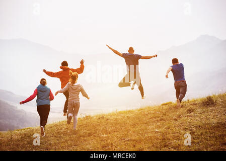 Five happy friends are having fun, runs and jumps against sunset mountains - Stock Photo