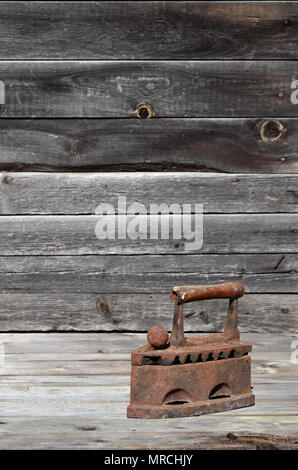 The heavy and rusty old coal iron lies on a wooden surface against the background of a  wall of black horizontal wooden boards. Obsolete device for ir - Stock Photo