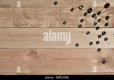 A few rusty nuts on a wooden background. Obsolete household tools made of rusty metal lie on a wooden table in a workshop. The concept of repair and c - Stock Photo
