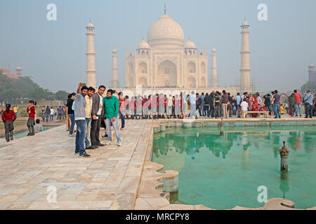 Agra, India - November 29, 2015: Famous Taj Mahal with visiting tourists - an immense mausoleum of white marble built by the Mughal emperor Shah Jahan - Stock Photo