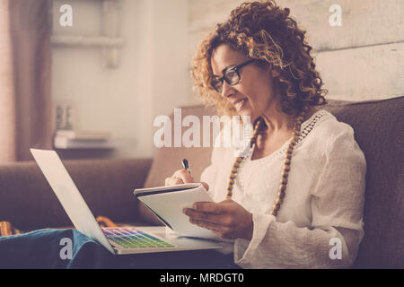 beautiful woman smile and write notes on paper working on a laptop freedom from office at home. alternative lifestyle and place to work on. vintage re - Stock Photo