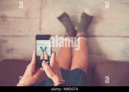 beautiful caucasian woman take picture with mobile phone at her legs against the wall with nice and funny socks. home alternative lifestyle and indepe - Stock Photo