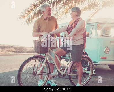 man and woman caucasian mature have fun outside with old bike and vintage van. vacation and happy retired concept. backlight from sun for nice models  - Stock Photo