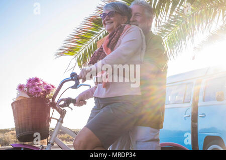 nice beautiful couple of seniors grandfathers going together on a bicycle outdoor in a tropical place. old vintage blue van in the background. happine - Stock Photo