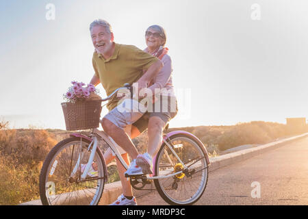 joy and happiness for adult married couple start and have fun traveling on the same bike in outdoor activity with sun backlight on the background. cle - Stock Photo