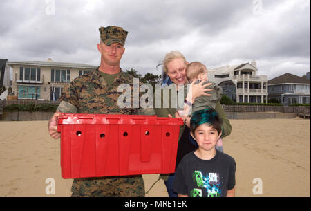 "170608-N-MS174-003 VIRGINIA BEACH, Va. (June 8, 2017) Gunnery Sgt. Paul Worley and his family escort ""Purple Heart,"" a Kemp's ridley sea turtle, to the beach prior to its release back into the Atlantic Ocean after being rehabilitated from a fishing hook. Worley, attached Command Marine Corps Security Cooperation Group at Joint Expeditionary Base Little Creek-Fort Story, is a Purple Heart recipient. ""Purple Heart"" is equipped with a U.S. Navy-funded satellite tag used to track the turtle's movements and the release was conducted as part of a Navy research project with the Virginia Aquarium and  - Stock Photo"