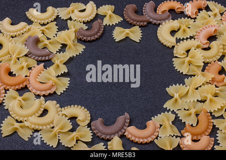 Variety of types of Italian pasta background. Set of raw dry pasta on a black slate background. - Stock Photo