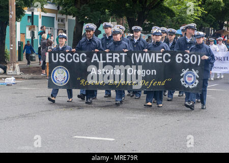 170610-N-ZP059-107 PORTLAND Ore., (June 10, 2017) – U.S Coast Guard members assigned to the medium endurance cutter Alert (WMEC-630) walk along the Rose Festival Parade route in Portland, Ore., during Portland Rose Festival Fleet Week. The festival and Portland Fleet Week are a celebration of the sea services with Sailors, Marines, and Coast Guard members from the U.S. and Canada making the city a port of call. (U.S. Navy photo by Mass Communication Specialist 2nd Class Jacob G. Sisco/Released) - Stock Photo