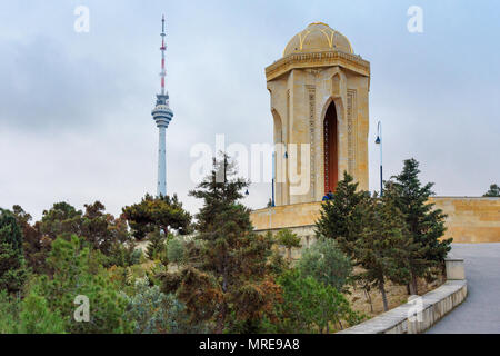 Baku, Azerbaijan - March 11, 2018: Shahidlar Monument or Eternal flame Monument on Martyrs' Lane. And Tv tower in the evening - Stock Photo
