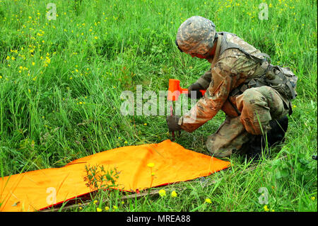 Pfc. Nicholas Timbrouck, a cannon crewmember assigned to the New York Army National Guard's  Alpha Battery, 1st Battalion, 258th Artillery Regiment, 27th Infantry Brigade Combat Team places a panel to mark the landing zone for a UH-60 Blackhawk helicopter during an air assault artillery raid at Fort Drum, N.Y. on  June 9, 2017. During the raid helicopters airlifted 4 of the battery's howitzers and transported them to a landing zone where they were then set up and utilized to engage a simulated enemy target. (U.S. Army National Guard photo by Sgt. Alexander Rector) - Stock Photo