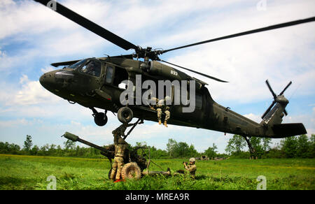 New York Army National Guard Soldiers assigned to Alpha Battery, 1st Battalion, 258th Field Artillery regiment, 27th Infantry Brigade Combat Team, prepare to attach a 105mm M119A2 Howitzer to UH-60 Blackhawk helicopter during a air assault artillery raid ,at Fort Drum on June 9, 2017 . The training mission was completed with 2 UH-60 Blackhawk helicopters provided by the3rd Battalion, 142nd Aviation Regiment. (U.S. Army National Guard photo by Sgt. Alexander Rector) - Stock Photo