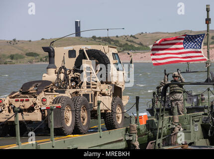 U.S Army Soldiers with the 200th Engineer, South Dakota Army National Guard, load military vehicles from the 1138th Transportation Company, Missouri Army National Guard on to an Improved Ribbon Bridge during a river crossing operation in support of Golden Coyote training exercise, Chamberlain, S.D., June 10, 2017. The Golden Coyote exercise is a three-phase, scenario-driven exercise conducted in the Black Hills of South Dakota and Wyoming, which enables commanders to focus on mission essential task requirements, warrior tasks and battle drills. - Stock Photo