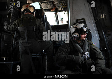 "(April 13, 2017) Naval Air Crewman (Helicopter) 2nd Class Stephen Prickett, right, watches the flight line as they lift off in an MH-53E Sea Dragon helicopter assigned to ""Vanguard"" of Helicopter Mine Countermeasures Squadron (HM) 14 during a formation and training flight. HM-14 maintains a worldwide 72-hour airborne mine countermeasures rapid deployment posture, a two aircraft forward-deployed AMCM and vertical onboard delivery capability in the 7th Fleet area of responsibility. - Stock Photo"