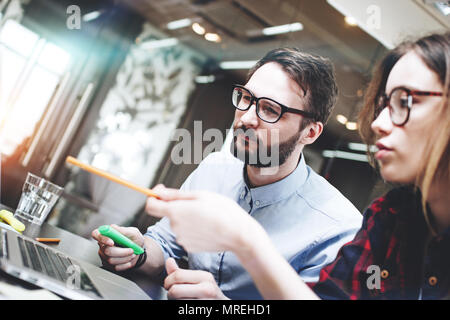 Team of businessman working on a new concept behind a modern laptop in open space office. Blurred background. Brainstorming a new startup - Stock Photo