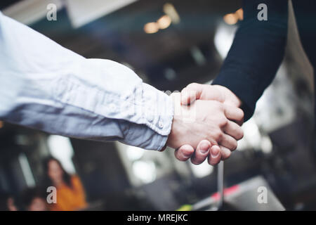 Two business partners shake hands after a successful deal. Close up view of business partnership handshake - Stock Photo