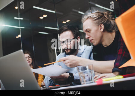 Team of young engineering students is working on a new project, discussing diagrams on paper and laptop in a modern loft space - Stock Photo