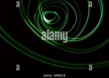 Glowing abstract curved lines. Green colors. Black background. Done by long exposure technique
