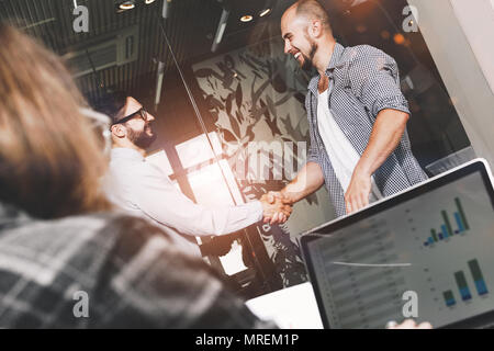 Group of young and modern businessmen have made deal and make handshake. Photo of two businessman handshaking process in loft space - Stock Photo