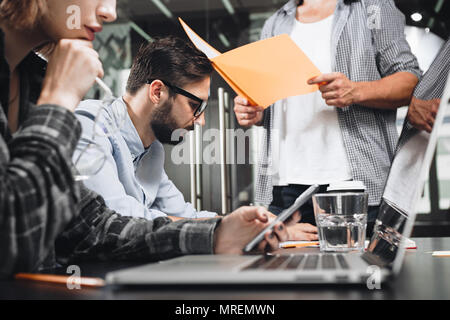 Team of friends or partners holds a business meeting in loft office. Business crew working with startup studio. Using digital tablet and gadgets - Stock Photo