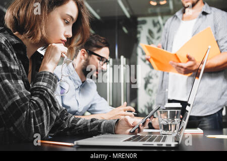 Team of modern startup managers works on laptop in loft space. Teamwork brainstorming concept. Analyzing new idea and developing plan - Stock Photo