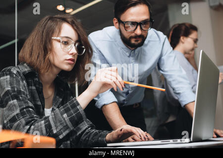 Team brainstorming. Business team of women and men in process of working on laptop. Contemporary notebook on wood table. - Stock Photo
