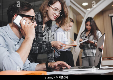 Teamwork concept. Coworking people work together in loft office. Bearded businessman talks on smartphone. Female manager holding presentation on lapto - Stock Photo