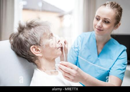 Care worker inserting nasal cannula in senior woman. - Stock Photo
