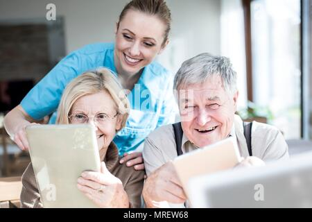 Senior couple using digital tablets in care home. - Stock Photo