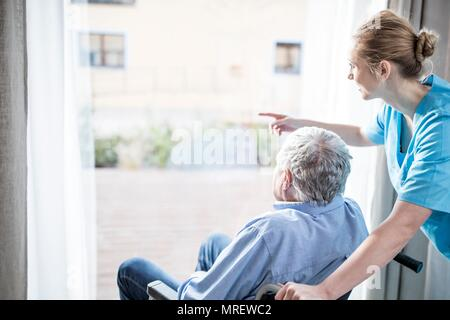 Senior man in wheelchair with care worker looking out of window. - Stock Photo