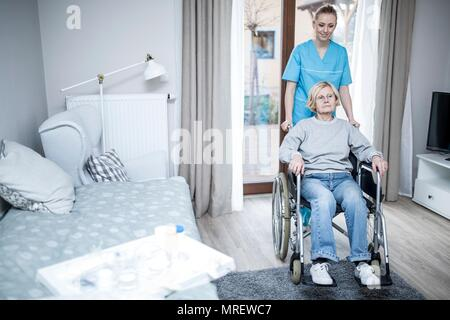 Senior woman in wheelchair with care worker in care home. - Stock Photo