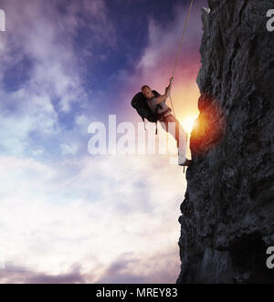 Man climbs a high danger mountain with a rope during sunset - Stock Photo