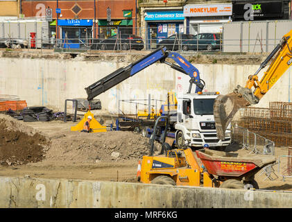 Dumper truck and lorry at work on the site of a new office development in Pontypridd town centre - Stock Photo