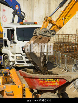Close up of an excavator bucket tipping earth into a dumper on the site of a new office development in Pontypridd town centre - Stock Photo