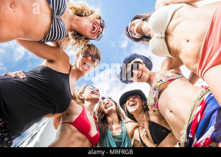 nice portrait of seven women females caucasian from the botton point of view in the middle of the group. people happy having fun together in relations - Stock Photo