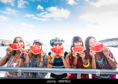 five nice happy young females caucasian eating watermelon to celebrate summer time and warm day with sun near the ocean. beautiful colors for group of - Stock Photo