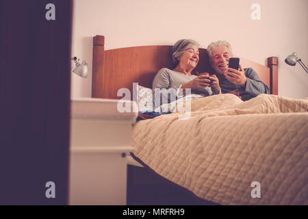 nice beautiful models couple of adult senior 70 years old having fun and enjoy in bed at home in bedroom. morning lazy wake up with no rush checking e - Stock Photo