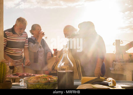 two matures adult couple caucasian people having fun enjoy the dinner time at the sunset on the rooftop terrace outdoor at home. golden tones for leis - Stock Photo