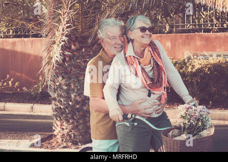 caucasian senior retired couple enjoy leisure activity outdoor hapy on a single bike two people going everywhere under the sun in vacation or new life - Stock Photo