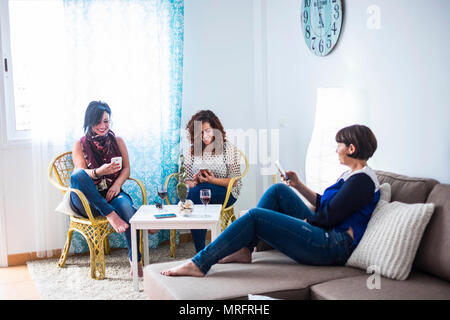 group of people three caucasian beautifl female friends stay at home using cellular smartphone together. everyone do his own activity work or leisure  - Stock Photo